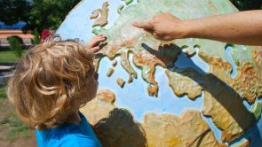 young boy pointing to a globe